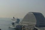 神戸港入港中の飛鳥II 後方に神戸空港着陸中の飛行機が見える